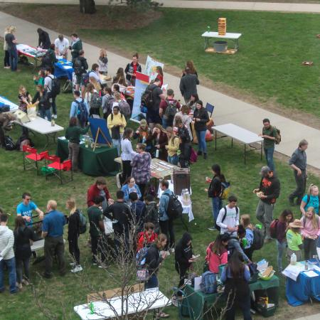 Students gather around tables and discuss sustainable topics at Celebrate Green event.
